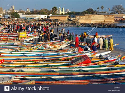 Colorfully painted fishing boats line the beach at the